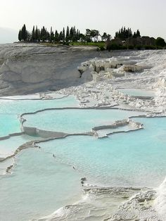 """PAMUKKALE - means """"cotton castle"""" in Turkish.  This travertine deposition at Pamukkale, one of Turkey's most important tourist destinations, has been in progress for at least the last 400,000 years, and has partially overwhelmed the Roman city and necropolis of Hierapolis. The travertine originates from hot waters that emerge at 35–56°C from open fissures and at least one fault zone."""