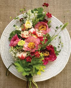 tree peonies, cosmos, tulips, and delicate wire vine to create a cascade that's meant to be draped over one arm.