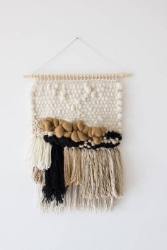 The delicacy of soft and smooth white texture combine with contrasting colors and textures and layers of fringe, makes this wall hanging visually interesting. Wall hanging made from merino roving, merino wool, wool blends and cotton. Colors: off white, nude, beige, camel, black. Colours are true but please be aware that there may be differences between my monitor and yours. Hung on a 40cm (16) long wooden dowel, this weaving hangs 53cm (21) long (longest point) and measures 34cm (13) wide…