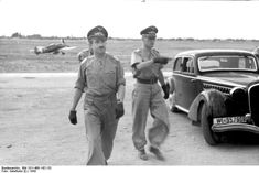 German Luftwaffe Major General Adolf Galland on an inspection in southern Italy, 1943; note Bf 109 fighter in background
