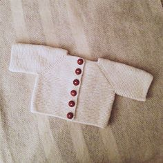 A winter white sweater with handmade buttons, knit from Quince and Co yarn.