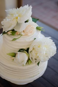 Wedding cake on natural wood table. Textured buttercream wedding cake. Cake decrated with white and peach tone flowers. Photo by: Buena Lane Photography