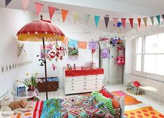 eclectic colourful childrens room. bird mobiles. red parasol with yellow tassels. flag banner. cinco de mayo themed banner.