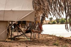 Man relaxing in tent by the river while on safari