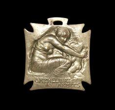 """Khalil Gibran: """"Protegedme de la sabiduría que no llora, de la filosofía que no ríe y de la grandeza que no se inclina ante los niños.""""  Medalla de latón (33 x 32 mm.) diseñada por R. Lalique en 1915 con el fin de captar recursos para el orfanato del ejército. Posee forma de cruz de malta y en ella aparece una figura femenina que abraza a dos niños y representa la Caridad protegiendo a la Infancia.  Imagen y catalogación: Yolanda Gil"""