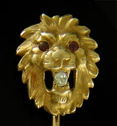 A lion roars while clutching a sparkling diamond in his mouth.  The lion's fierce aspect is accented with fiery red eyes (likely rubies or garnets).  Crafted in 14kt gold,  circa 1900.