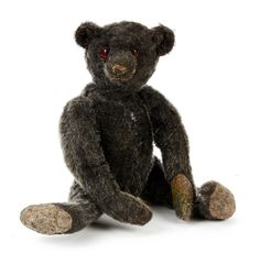 Rare early frosted black Bear, poss Strunz or American boot button eyes, black stitched nose & mouth, jointed elongated limbs with grey felt pads and five brown stitched claws and hump, circa 1909 - 11.25in high (replaced ears, slight repair to left leg, wear and patch to left hand pad). Notes: This bear, probably during his restoration given red felt backing eyes, in the belief that he may have been Steiff. It is very unusual to find any bear, especially this early in a black mohair