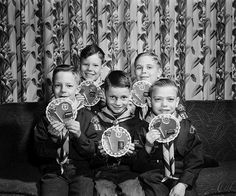 A group of young Cub Scouts posing with their handmade Valentine's Day cards