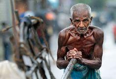 An Honest Day's Work. An elderly Sri Lankan laborer pushes a cart as it rains in Colombo, Sri Lanka, on Sept. 4