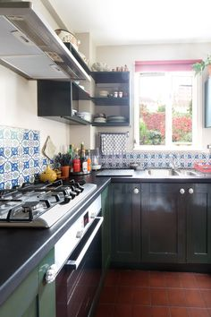 Paint: Farrow & Ball's Elephant's Breath on walls, Farrow & Ball's Studio Green on kitchen cabinets. Blackboard paint on worktop. 'Flame Red' quarry tiles on floor, £1.07 each from Fired Earth.