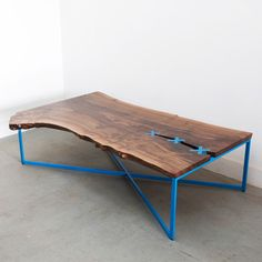 Interesting Coffee Table - Stitch by Uhuru Design | The top is made of a wooden slab with a naturally occurring split. Held together by four stitches made of recycled plastic, it sits a top a matching base made of powder coated blackened steel. Because each wood slab is locally milled and dried, no two tables are exactly alike, ensuring a unique piece every time. |