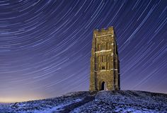 Glastonbury Tor Startrails - A clear chilly winter night at Glastonbury Tor on the Somerset Levels. The startrails are a result of a very long exposure time capturing the movement as the earth rotates creating this star trail effect.