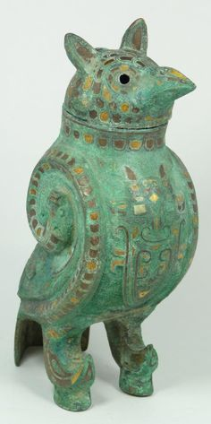This extremely rare bronze wine container is inlayed with silver, gold and copper. The total surface is covered with cupric oxides due to extended burial. The back as well as both sides of the object depicts coiled serpents and archaic style birds, while the chest shows an inlaid mythical horn animal against a lewien pattern ground. The removable head is also inlayed with gold and silver giving the appearance of layered feathers. From the Warring states period (475-221BC)