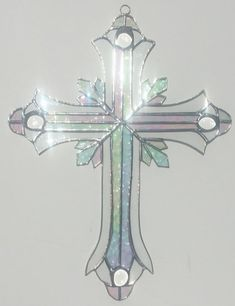 This ornate cross features a center of iridescent glass, with an outline of clear glass. Iridescent diagonal points extend from the center, and the points of the cross are adorned with clear glass jew