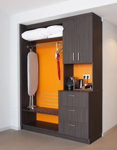 Hotel room interior with a refreshing orange color and practical closet solution. Interior architecture | Ramsoskar