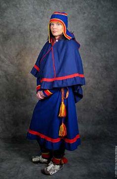 Samedräkt för kvinna med luhkka, oväderskrage/cape och muffal, yttermössa som används till Gällivare/Jukkas samedräkt. Woman wearing an outer garment a cape, luhkka, and a outer garment hat, muffal, that belongs to the female Saami kirtle known as Gällivare - Jukkas Saami kirtle.