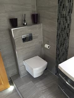 Wall hung toilet pan, raised flooring into the room, with chrome edging bead to frame the stunning grey tiles