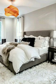 gray and white master bedroom with light gray walls and white fur rug