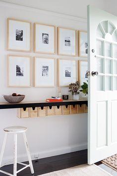 decoração de hall de entrada com prateleira como aparador e quadros em preto e branco com moldura em amdeira cru na parede