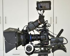 "What's on this Canon C100 Rig? 1) Matte box: the barn door-lookin' things on the front help us control the amount of light that goes into the lens. 2) Follow focus: the white circular piece allows us to ""pull"" or change focus slowly and smoothly for cinematic looking shots. 3) Monitor: allows us to compose shots with an eagle eye ('cause peeking through the tiny viewfinder gets tougher every year older we get!) #PinkWeddingFilms"