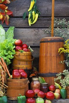 Butter churn and antique buckets sit beside barn with fall harvest apples