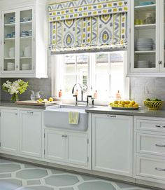 gorgeous kitchen - White Shaker cabinets, grey concrete counters, grey marble backsplash, mod bridge faucet, Roman shade, yellow and blue accents
