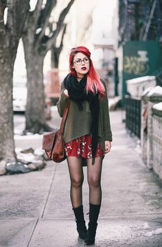 Le Happy wearing chunky green sweater and red floral dress