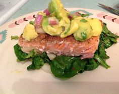 Avocado salsa topped salmon over sautéed greens....