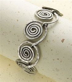 Textured spiral links with a matching clasp. From Step by Step Wire Jewelry, April/May 2010.#wire #jewelry #spirals by larry whitfield