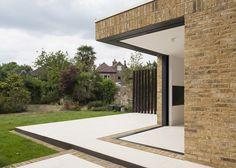 This London house extension by Tigg Coll Architects features sliding glass doors that retract into the brick walls to open the space up to the garden.