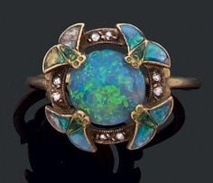 Ring, attributed to Eugen Feuillatre, in yellow gold with a round opal adorned with blue green enamel winged insects, surround by openwork set with roses, circa 1900