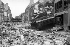 Carcasse du Tiger Nr. 121 (modèle tardif) commandé par le SS-Hauptsturmfuhrer Möbius du 1./schwere SS-Panzer-Abteilung 101 détruit dans les ruines de Villers-Bocage, rue Pasteur, après la bataille du même nom. Un tir de 6-pounder britannique aura eu raison du char lourd peu à l'aise en milieu urbain.  Derrière lui se trouvent le Tiger 112 ainsi qu'un des 5 Panzer IV détruits pendant la bataille (celui-ci appartient à la 130. Panzer-Lehr-Division.  6 Tiger seront mis hors de combat dont 3…