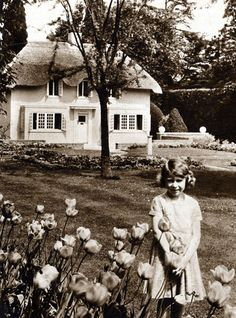 A young Princess Elizabeth poses in front of The Little House at the Royal Lodge.  the playhouse gifted to her and is still used by her grandchildren.