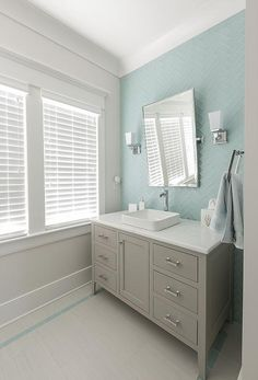Calming gray and blue bathroom features a gray washstand fitted with satin nickel pulls and a honed white marble countertop finished with a square vessel sink fixed under a rectangular pivot vanity mirror mounted on blue glass herringbone backsplash tiles lit by nickel uplight sconces.