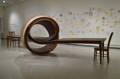 Not Now, an enormous conference table that loops in the center. By artist Michael Beitz,a 28 foot long sculpture made from wood.