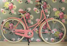 Pink retro bike and vintage floral wallpaper