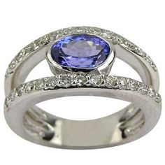 In this particular contemporary ring, a split shank has brilliant round diamonds and an oval, lavender bezel-set tanzanite.