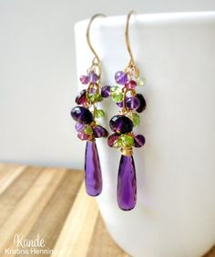 Purple amethyst, lime green peridot, and berry red rhodolite garnet gemstones are hand wrapped with 14k gold fill wire and dangle from a 14k gold fill chain. Handmade 14k gold fill ear wires. The Mila Earrings are approximately 2 3/4 inches long. See more designs at kande.etsy.com All