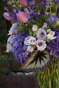 Radiant Orchid, purple and green with tulips, purple hydrangea, Little Silver spray rose, purple delphinium and begonia leaf  for bridal shower by Fleur de Vie.