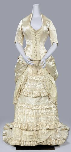 Wedding dress ca. 1880. Silk. Bustled skirt with train. Rijksmuseum: There was a great fondness for excessive use of fabric around 1880, both in fashion and in interiors. In the latter, this was expressed in highly pleated and draped curtains and seating. Click through for larger pic.