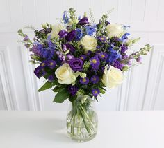 The Mayfair Bouquet: • 5 Delphinium • 5 Aster blue • 5 Purple lisianthus • 3 Green bell • 5 Lilac stocks • 5 White Avalanche rose