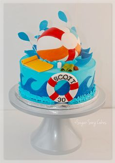 6 ball splashing into a 10 buttercream tier.  Fondant covered ball and wired splashes, fondant/gum paste pool float, drink, trunks and lotion.