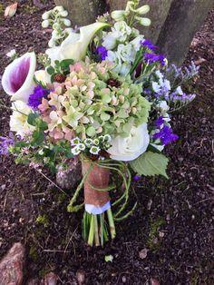 Bridal bouquet with green hydrangea, dark purple mini callas, wild flowers and little pine come accents