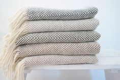 Fresh off the loom: Our handmade 100% pure wool throws will keep you warm and cozy. Handwoven in a herringbone pattern, these throws are beautiful to wrap yourself up in or to use as an accent piece in your home. Made in our home base studio on a shuttle loom, these throws subtly combine a feeling of tradition with modern design. These herringbone throws measure approximately 56 x 44, not including the 5 hand twisted and knotted fringes on either end, which are made up of 500 individual…