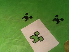 Cheap green plastic tablecloth...black sharpie and a paper-cut stencil and hey presto...Minecraft Tablecloth for the birthday boy!