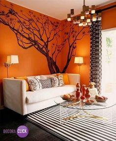 Escolher laranja na sua sala de estar é uma ótima opção, observem a alegria que a cor trouxe ao ambiente. O desenho na parede e o tapete fizeram toda a diferença para completar essa vivacidade.