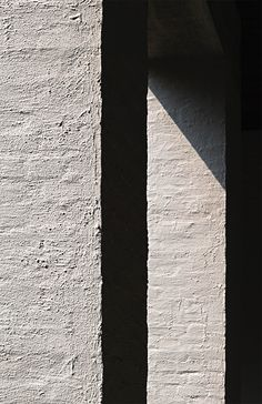 The materiality of architecture brought to life by the sun. Rendered stone of the Vaals abbey by Dom Hans van der Laan. Photo by NOMAA|marco jongmans.