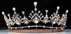 A gorgeous diamond and pearl tiara, 1880, in the festoon style. Featuring at least five larger diamond and pearl motifs, with a button pearl in the lower foliate, then topped with a baroque pearl, with smaller diamond spacers, each topped with a circular diamond.