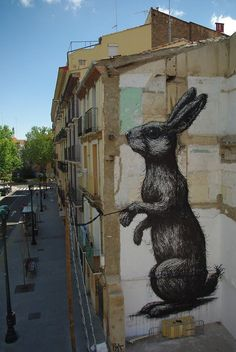 The Belgian street artist ROA adorns the urban environment with giant black and white animals such as this rabbit