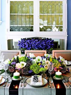 The tabletop holds a long hedge of hydrangeas, white amaryllis, purple statice, mixed evergreens, fresh pears and white-tipped pinecones, al...